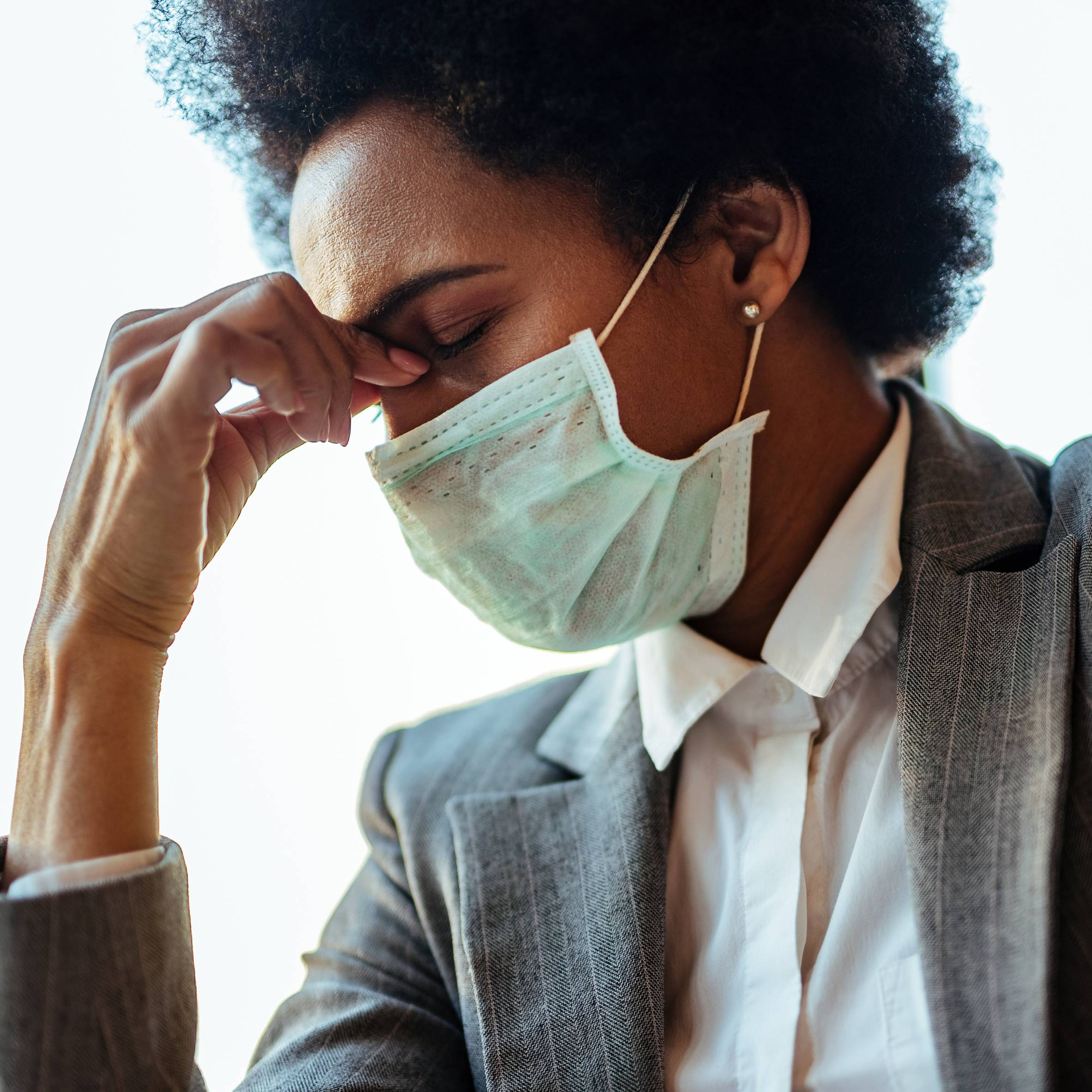 A Photo Of An Exhausted Black Businesswoman Fighting A Migraine, As Evident By Her Grasping The Bridge Of Her Nose. The Woman Is Wearing A Face Mask To Protect Herself From COVID.